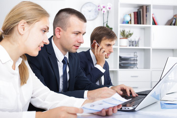 young man manager working with concentrated colleagues in office