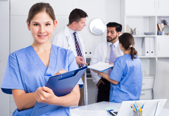 Female doctor writing notes on clipboard
