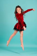 Little girl dancer jump on blue background