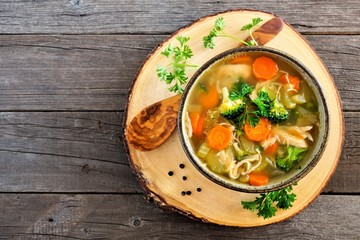 Homemade chicken vegetable soup, in a clay bowl with wooden server. Above view on a rustic wood background.