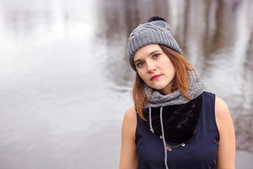 young woman standing by the water in the cold
