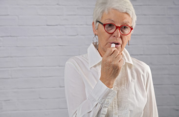 Portrait of attractive elderly woman applying lipstick. Older beauty, Short hairstyles, Aging gracefully concept
