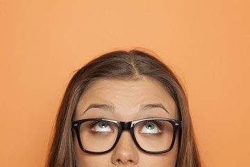 half portrait of a young girl with glasses looking up