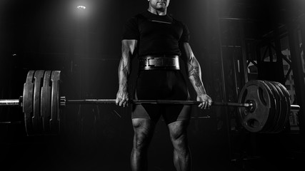 Professional athlete is standing and is holding a very heavy barbell.