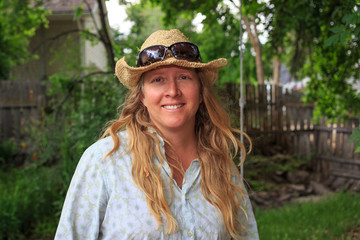 Outdoor portrait of an everyday blond woman wearing a straw hat.