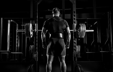 Professional athlete stands in front of the bars with a barbell and is about to crouch with her.