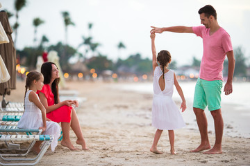 Parents and adorable two kids have a lot of fun during their summer vacation on the beach. Family of four in love, happy and beautiful.