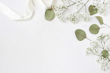 Styled stock photo. Feminine wedding desktop mockup with baby's breath Gypsophila flowers, dry green eucalyptus leaves, satin ribbon and white background. Empty space. Top view. Picture for blog. Wall mural