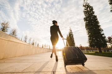 woman stewardess in the form of carrying a suitcase