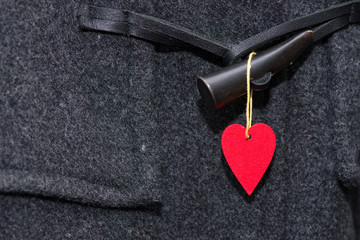 Red heart hanging on a button of a coat