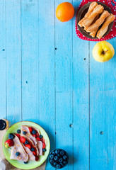 Fresh homemade crepes served on a plate with strawberries and blueberries, on a light blue wooden background,  free space for text.