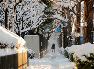 A woman and her baby make their way on a snow-covered sidewalk in Tokyo