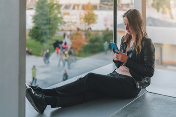 Young woman sits on floor near large window and uses smartphone.Hipster girl looking on screen of phone,blogging,chatting,browsing internet. Online marketing, education, distance work. Social network.