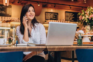 Young businesswoman dressed in white shirt is sitting in cafe at wooden table in front of laptop and talking on cell phone. Telephone conversations. Hipster girl is talking on phone with her friend.
