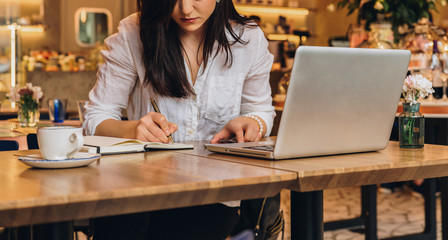 Young businesswoman is sitting in cafe at table in front of laptop, working, making notes in her notebook. Student girl learning online, writing conspectus. Online marketing, education, e-learning.