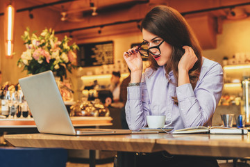 Side view. Young business woman is sitting in cafe at table in front of laptop and looks at screen in surprise, lowering her glasses. Hipster girl blogging, learning online. Distance work, education.