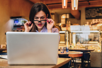 Front view. Young business woman is sitting in cafe at table in front of laptop and looks at screen in surprise, lowering her glasses. Hipster girl blogging, learning online. Distance work, education.