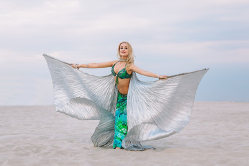 A beautiful blond girl in a golden with green dress with wings, suit is dancing an oriental, East dance in the desert on the sand. Beautiful exotic woman dancer in a costume for belly dancing.