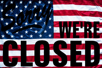 government shutdown represented by a sorry we're closed sign outline with american flag background