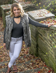Beautiful Caucasian female model poses wearing a faux fur vest and white pants stands in outdoors stairs in autumn (dramatic side lighting)