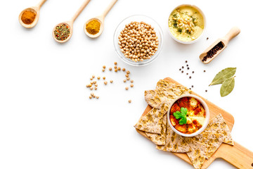 Middle Eastern cuisine. Bowl with hummus among pieces of crispbread and spices on white background top view copy space
