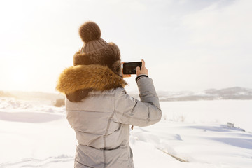 woman is photographing on the phone a snow-covered field