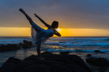 Young Girl Ballet Dancer on beach rocky coastline pose leap silhouetted dawn sunrise