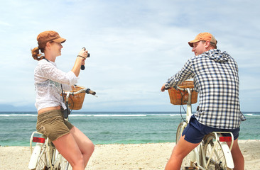 Cheerful couple is having rest and taking pictures in the beach with old fashioned bicycles.