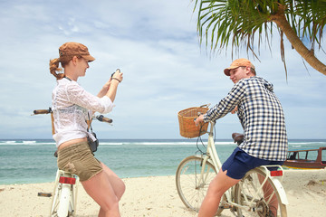 Cheerful woman is having taking pictures her boyfriend in the coast with old fashioned bicycle.