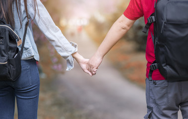 Young couple  walking in the autumn park holding hands and looking in the sunset
