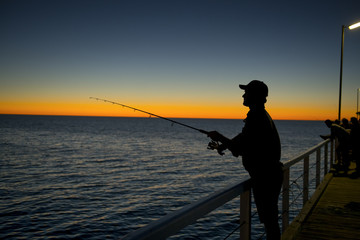 silhouette of fisherman with hat and fish rod standing on sea dock fishing at sunset with beautiful orange sky in vacations relax hobby