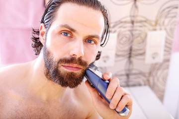 Handsome young man shaving his beard with electric shaver