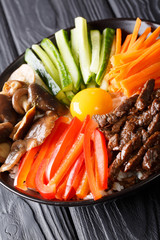 Delicious Korean food Bibimbap with beef, yolk, vegetables, mushrooms and rice close-up in a bowl on the table. vertical