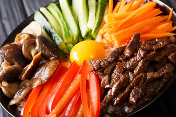 Bibimbap with beef, yolk, vegetables, mushrooms and rice macro. horizontal