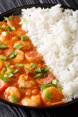 New Orleans gambo with shrimps and sausage close-up in a plate on the table. vertical