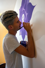 Young artist painting the mandala on the wall
