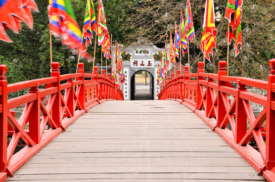 Red wooden Huc Bridge from the Ngoc Son Temple in Hanoi Vietnam leading to  the exit door.  Flags waving in the wind on the banisters left and right.
