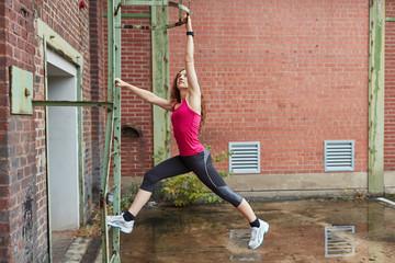 Junge aktive Frau beim Gebäudeklettern