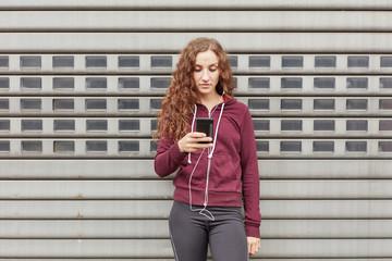 Sportliche junge Frau benutzt Fitness App