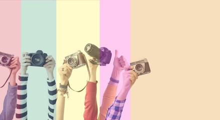 Different color hands holding cameras in front of colorful background