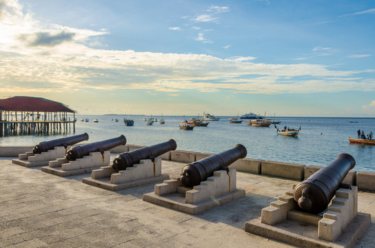 Five cannons in line at the waterfront in Stone Town Zanzibar. Several fishing boats are anchored off shore in the ocean. It's a tranquil scene at sunset with few clouds in the sky