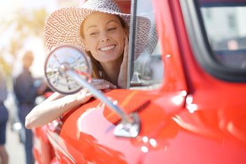 Portrait of beautiful woman in vintage red truck