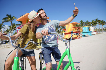 Young couple riding bikes in Miami beach, taking selfie pictures