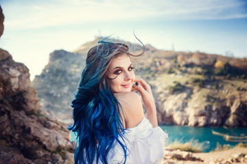 Young woman standing on cliff's edge and looking into a wide sea view. Wind Long Blue hair hairstyle.
