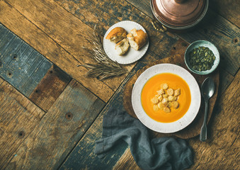 Flat-lay of fall warming pumpkin cream soup with croutons and seeds on board over rustic wooden background, top view, copy space. Autumn vegetarian, vegan, healthy comfort food concept