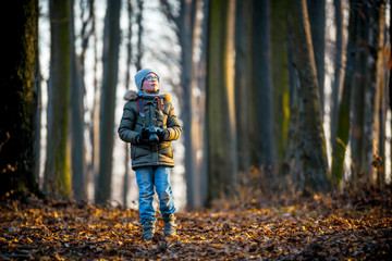 Boy with digital camera walking in the nature, hobby concept