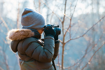 Boy using digital camera taking photo in the nature, hobby concept