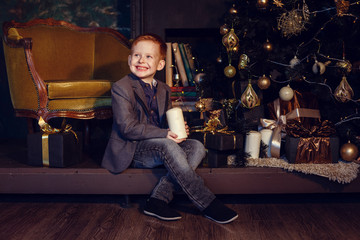A little boy with red hair and freckles on a dark background. Gold and black. Christmas Tree and New Year Decorations