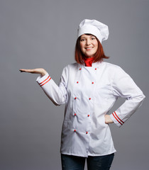 Photo of smiling brunette chef in white robe with empty palm