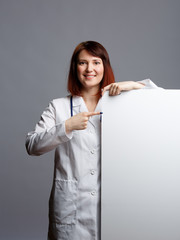 Image of smiling female doctor in white robe and with phonendoscope points finger at blank paper